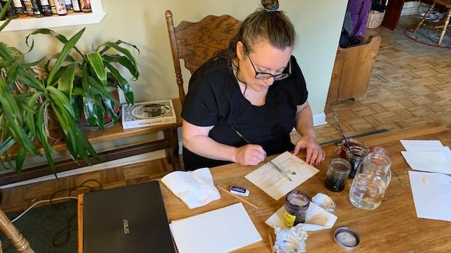 L'artiste est assise et peinture à sa table de cuisine avec des esquisses et des pots d'encres.