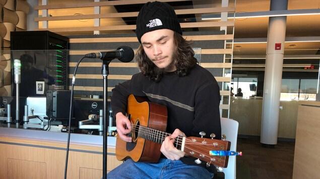 Jacques Surette assis sur un tabouret et jouant de la guitare.