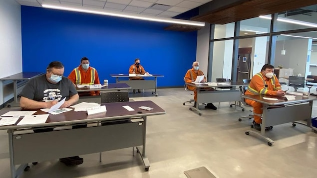Cinq formateurs assis à leur bureau assistent à la formation.