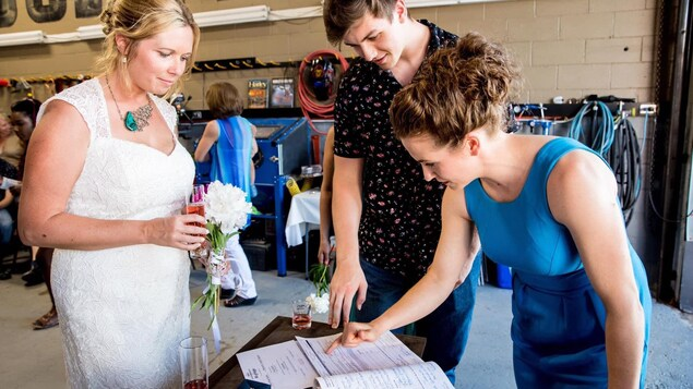 Elle est devant les documents avec la mariée et un jeune homme à la chemise fleurie.