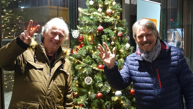 Jean-Guy « Chuck » Labelle et Robert Paquette saluent la caméra dans les locaux de Radio-Canada, près d'un sapin de Noël