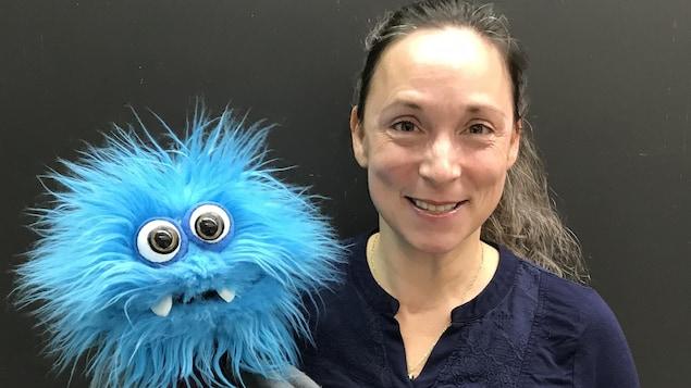 Elle pose, marionnette bleue et chevelu à la main.