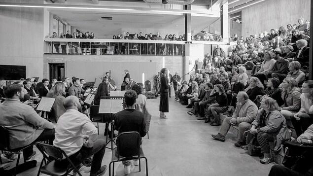 Musiciens, maître d'orchestre et le public lors d'une prestation à l'École d'architecture au centre-ville.