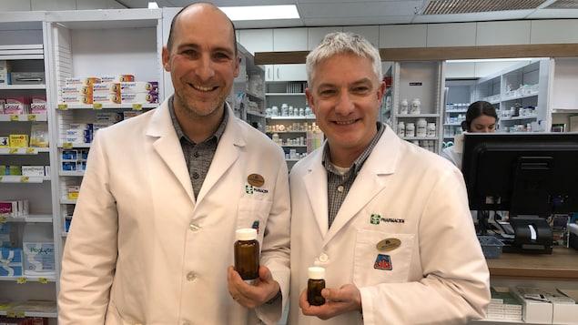 Deux pharmaciens photographiés avec des bouteilles de vitre.