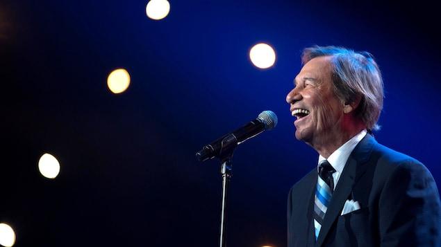 Jean-Pierre Ferland devant un micro chante avec un sourire.