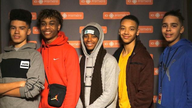 Les cinq jeunes devant le mur aux logos d'ICI Première.