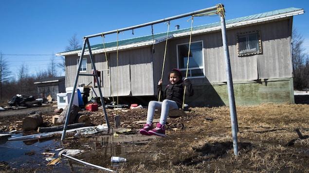 Une enfant joue sur une balançoire à l'arrière d'une maison dans une cour jonchée de déchets.