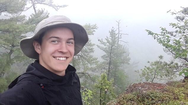 Un jeune homme souriant devant une forêt couverte de brouillard.