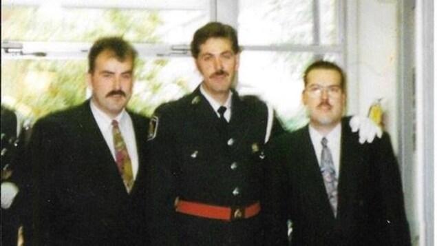 Trois hommes posent côte-à-côte; l'homme au milieu porte un uniforme de policier.