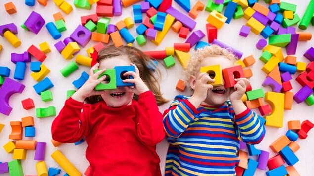 Des enfants d'âge préscolaire, couchés sur le dos, jouent avec des blocs de jouets en plastique colorés.