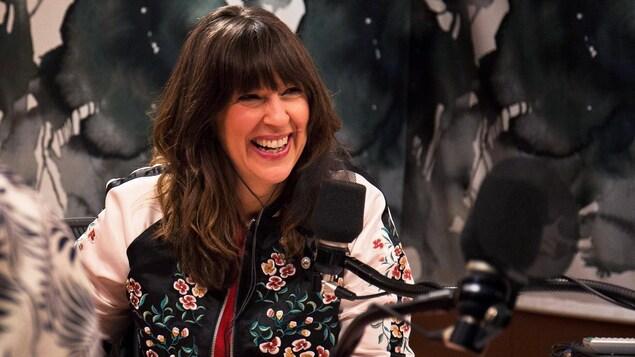 L'animatrice sourit pendant la diffusion de son émission Plus on est de fous, plus on lit