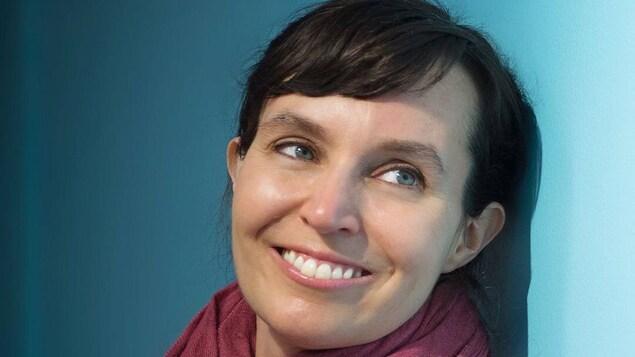 Un femme est photographiée appuyée sur un mur, en gros plan.