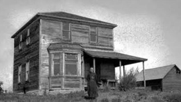 Photo noir et blanch d'une maison en bois, une femme à l'avant.