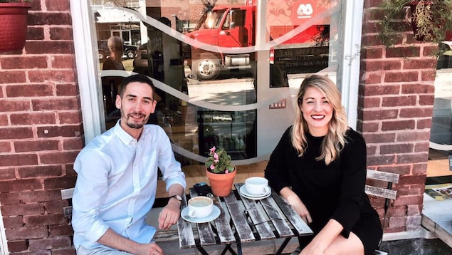 Justin Johnson, président de la Fédération de la jeunesse canadienne-française et Mélanie Joly, ministre du Patrimoine canadien attablés au café  Postal, à St-Boniface, au Manitoba
