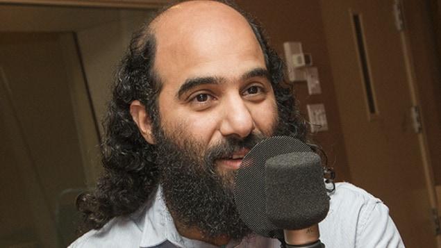 Un homme est photographié dans un studio de radio, devant un micro.