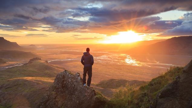 Un homme regarde un couché de soleil dans les montagnes