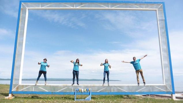 Quatre personnes vêtues de bleu se tiennent devant le fleuve.