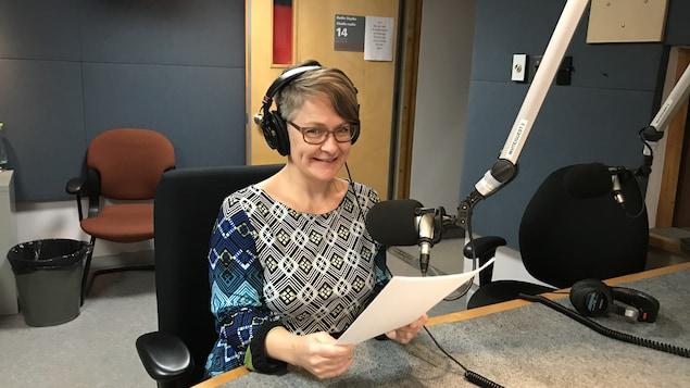 Une femme souriante assis dans un studio de radio.