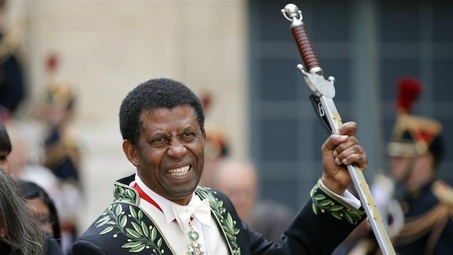 Dany Laferrière tenant son épée d'apparat de l'Académie française