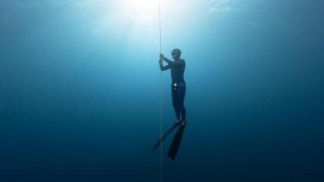 Un plongeur en apnée se tient sur corde en profondeur.