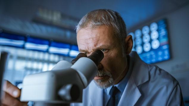 Un homme barbu et grisonnant observe quelque chose à l'aide d'un microscope, dans une grande salle de laboratoire un peu sombre.