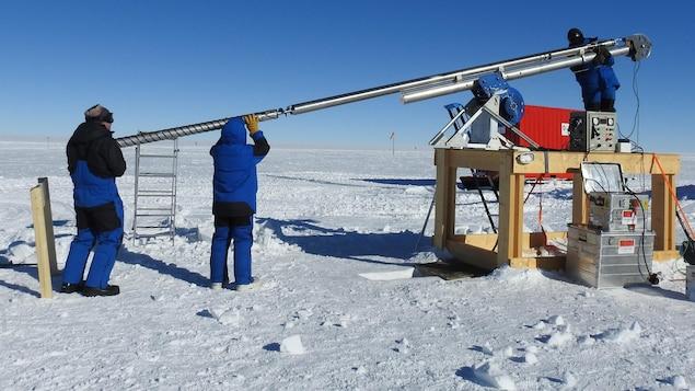 Trois personnes, habillées de survêtements d'hiver très chaud, manipulent une lourde tige de métal en vrille, au milieu d'une vaste étendue polaire de neige.