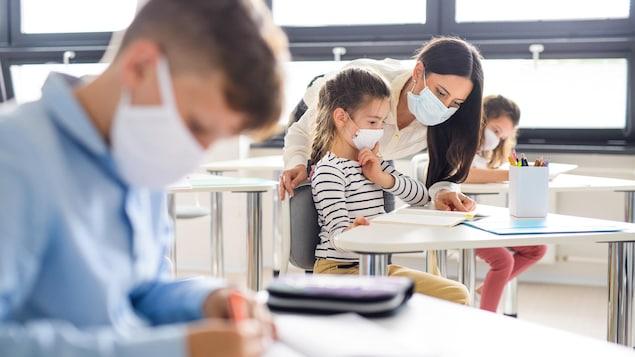 Un groupe de jeunes élèves portant un masque et assis en classe.