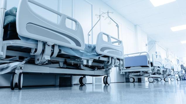 Des lits d'hôpitaux alignés dans un corridor.