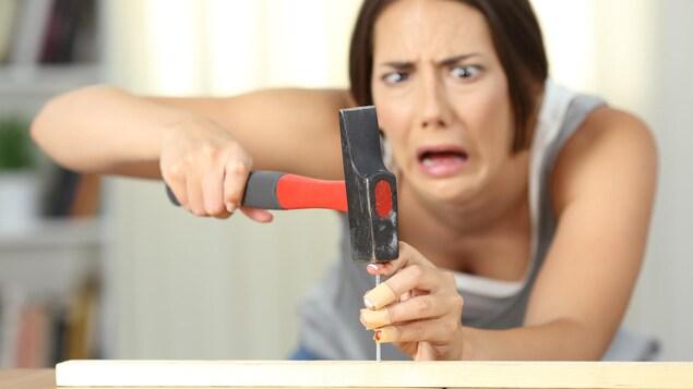 Une femme se cogne le doigt avec un marteau.