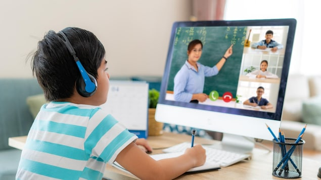 Un garçon devant un ordinateur assiste au cours donné par son professeure.