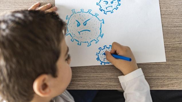 Un jeune garçon dessine un coronavirus.