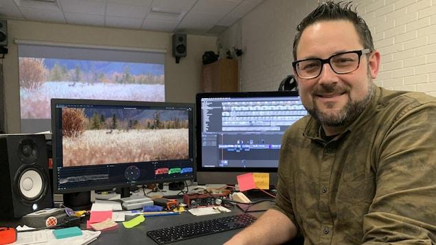 Un homme dans la quarantaine, barbu et portant des lunettes, pose devant un écran dans une salle de montage vidéo.