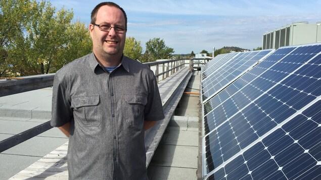 Un homme portant des lunettes, dans la quarantaine, regarde la caméra alors qu'il se trouve debout, à côté d'une rangée de panneaux solaires, sur le toit d'un bâtiment.