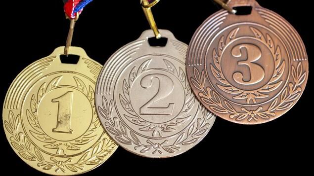 Les médailles d'or, d'argent et de bronze alignées sur un fond noir.