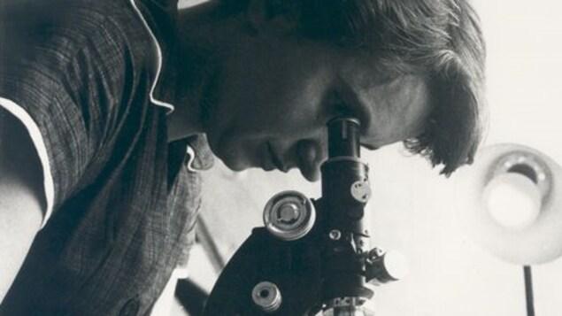 Rosalind Franklin à un microscope.