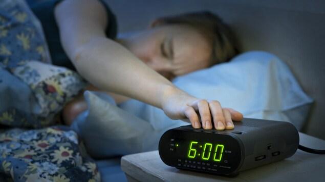 Une femme met la main sur son réveil-matin.