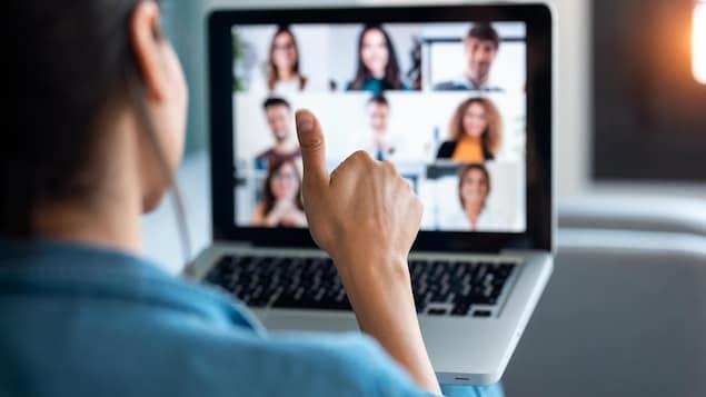 Une femme réagit le pouce en l'air devant l'écran d'ordinateur sur lequel apparaissent ses collègues de travail.