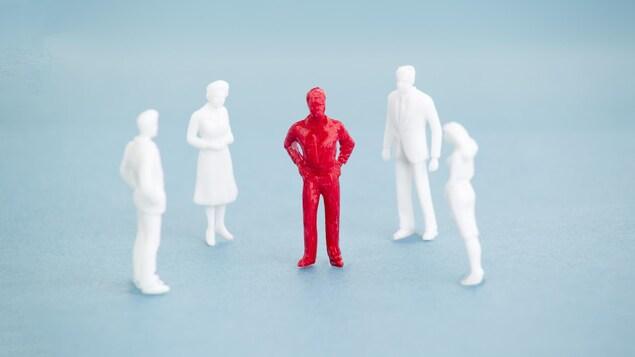 La figurine rouge d'un homme entourée de figurines blanches.