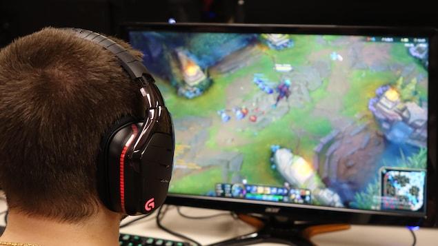 Un jeune homme joue à League of Legends sur un ordinateur.