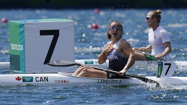 À bord de son kayak, Andréanne Langlois a l'air surprise et contente. Elle a la bouche ouverte et sa main droite est sur son coeur.