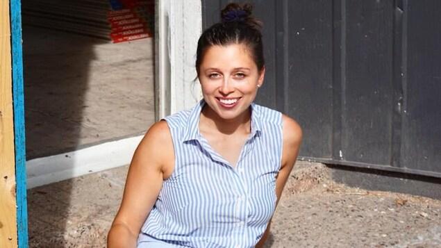 Lara Cusson est assise au sol avec derrière elle, son commerce en rénovation.