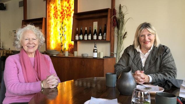 Michelle Labrèche-Larouche (à gauche) et Danielle Ouimet (à droite) assises à une table dans un restaurant, posent pour la caméra.