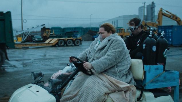 Une femme sur une voiturette de golf, sous des couverture, avec un plongeur et des bonbonne dans une zone industriel.