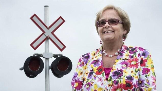 Colette Roy Laroche pose en souriant devant un panneau de signalisation ferroviaire