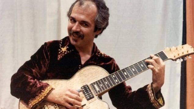 Il joue de la guitare dans une chemise de velours dans les années 70.
