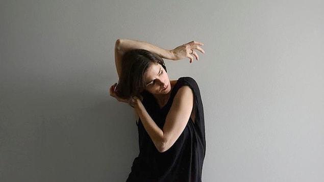 Une danseuse a la tête penchée, en appui sur sa main gauche, avec son bras droit croisé au-dessus de sa tête.