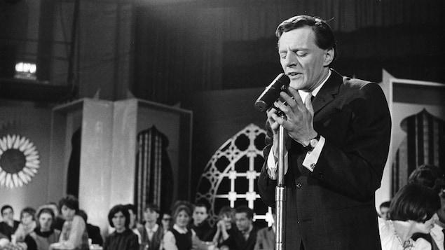 Claude Léveillée chante avec intensité debout dans une salle de spectacle en 1964.