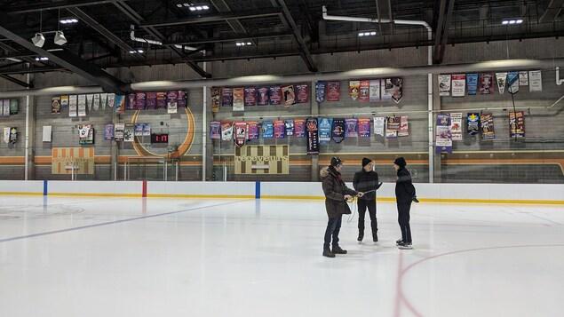 Sur une patinoire, un technicien tient un micro-perche entre un homme et une femme, les deux sur patins, qui discutent.