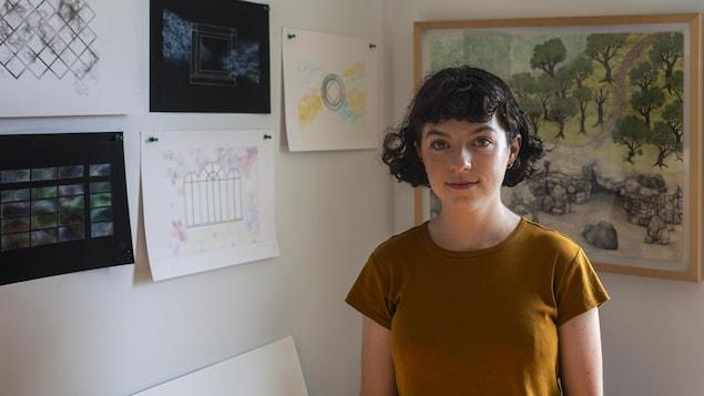 Lisa Theriault devant des tableaux accrochés au mur.