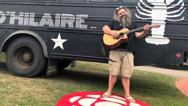 Serge Brideau pose une guitare à la main, devant le bus de son groupe Les Hôtesses d'Hilaire.